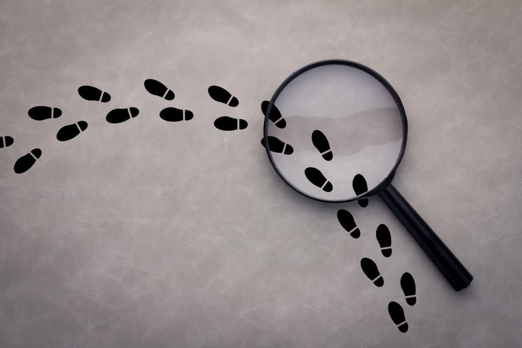 Magnifying glass over footsteps