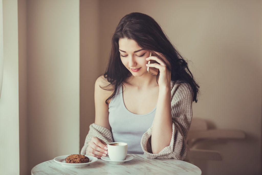 Woman with smart phone in cafe