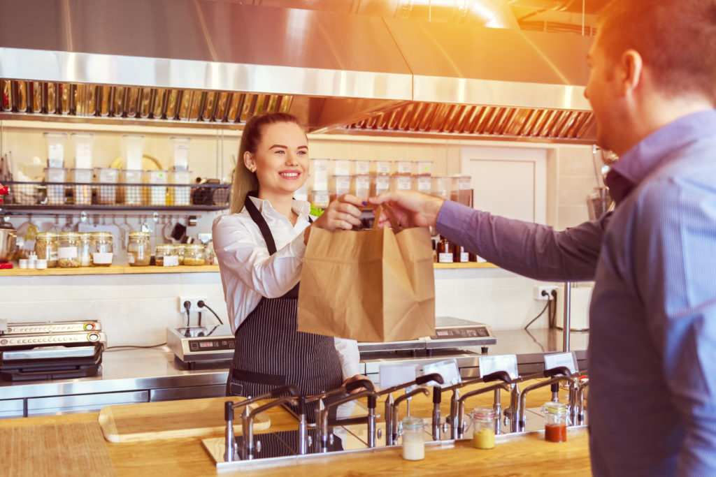 Cheerful waitress wearing apron serving customer at counter in restaurant - Small business and service concept with young woman owner giving eco friendly paper bag with take away food to online client