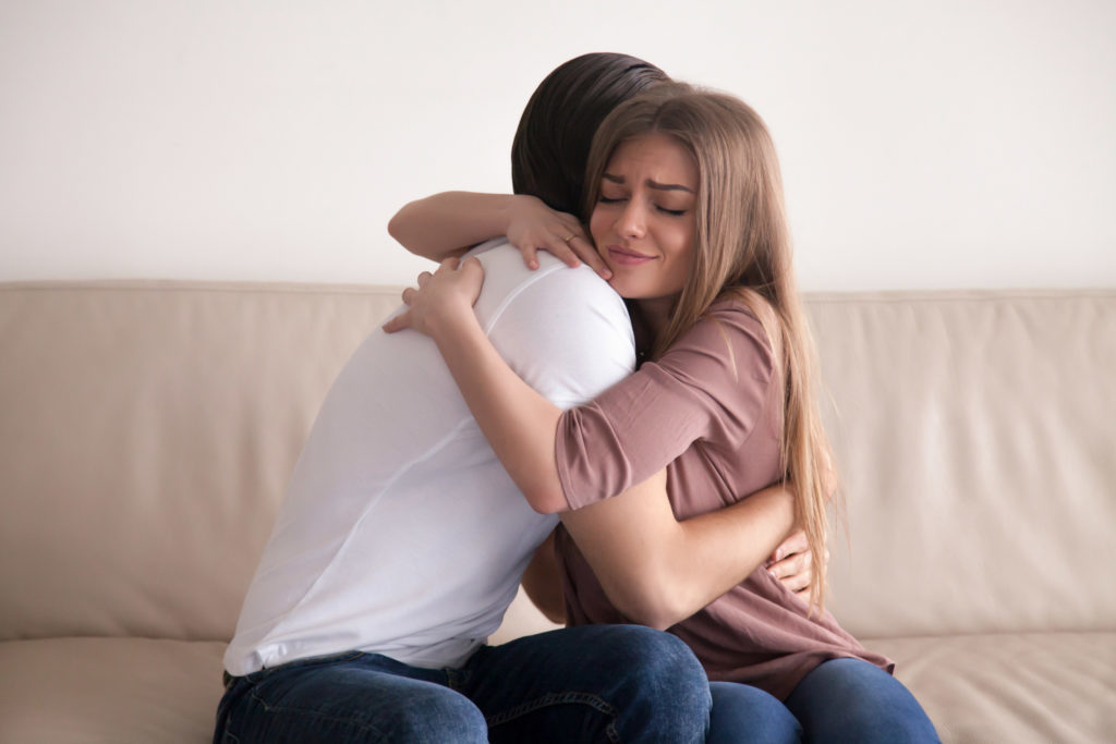 Portrait of emotional young couple hugging each other tightly, boyfriend and girlfriend embracing sitting on couch, reconciliation after argument, love you so much, strong affection in relationships
