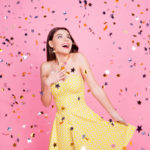 People victory luck fortune concept. Portrait of tender gentle cute lovely sweet pretty charming girl holding bottom of dotted dress with naked shoulders looking up confetti rain isolated background